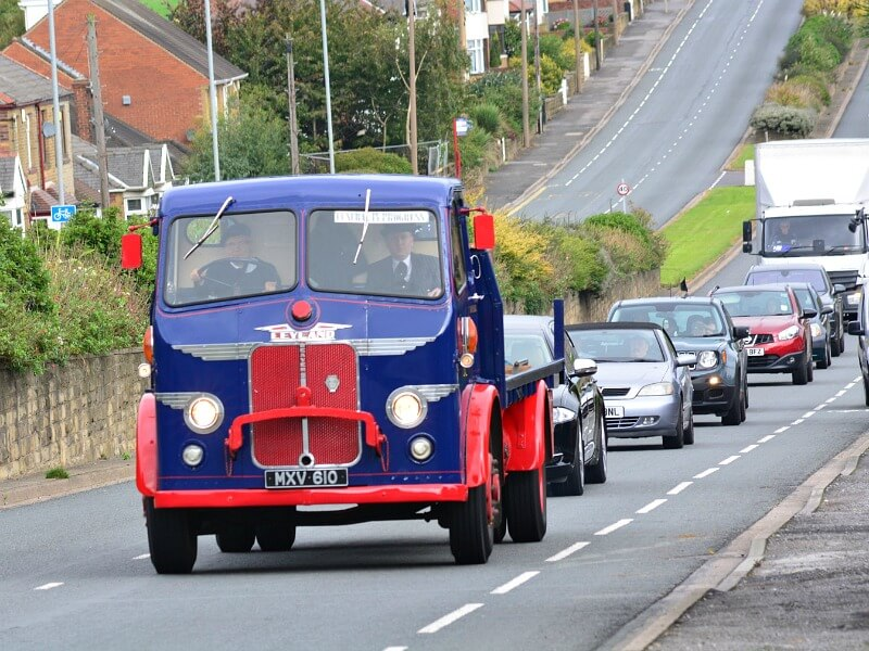 A blue and red lorry dating back to the 1950s leads a funeral procession