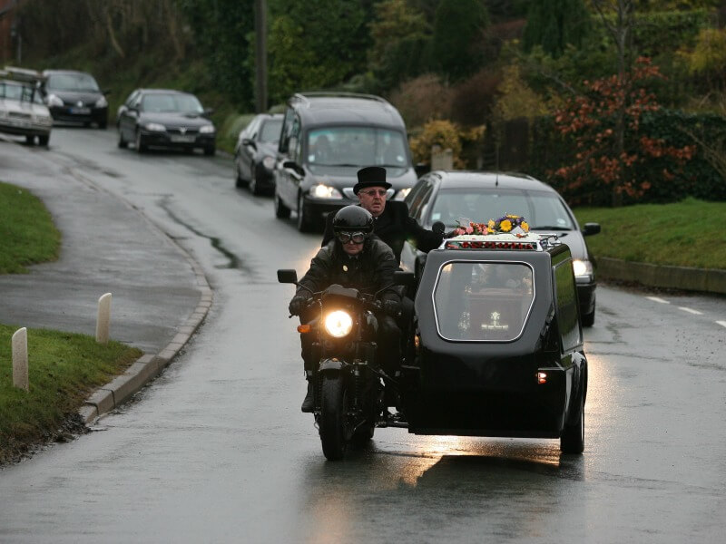 A motorcycle hearse and cortege driving down a road carriageway ona  rainy day