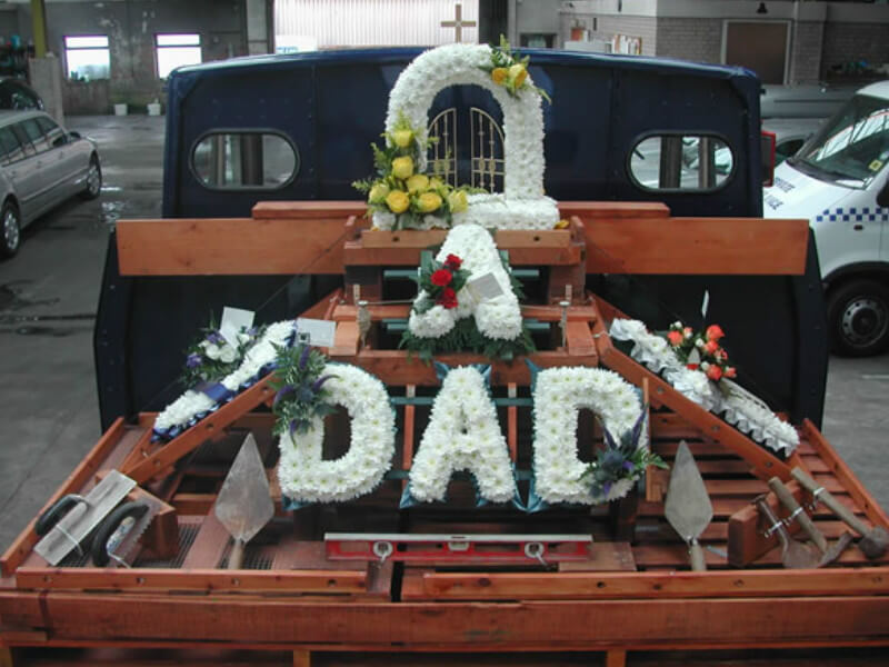 A funeral tribute displayed on the deck of a vintage lorry, commemorating someone who worked in the building trade
