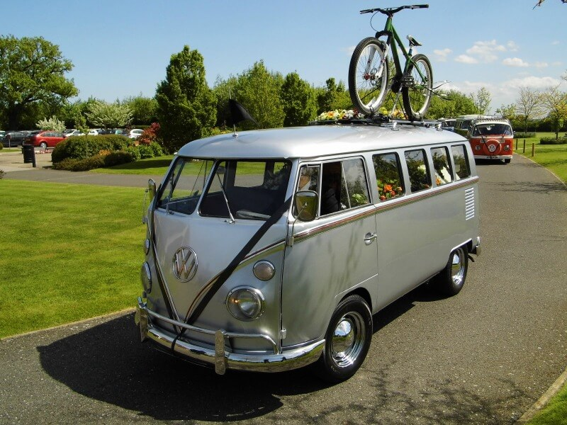 A cyclist is commemorated with a bike attached to the roof of their VW camper van hearse