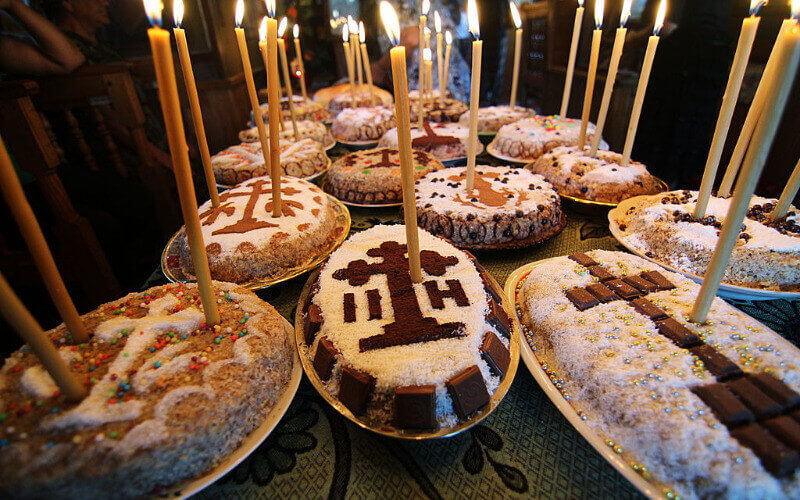 Lots of bowls of Koliva on a table, decorated with candy and candles