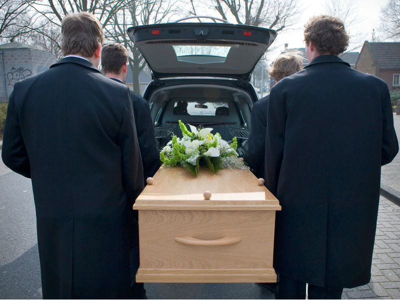 a coffin being placed in a hearse