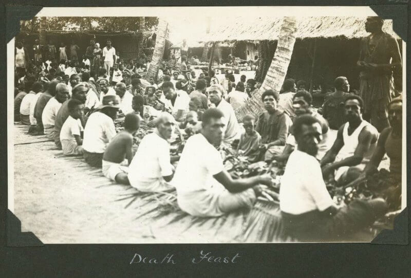 A crowd of people, sat cross-legged on the floor, eating a large funeral feast