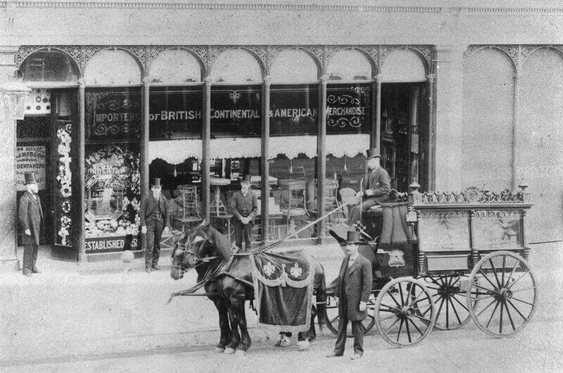 An elaborate horse-drawn hearse outside a shopfront in Brisbane in 1892