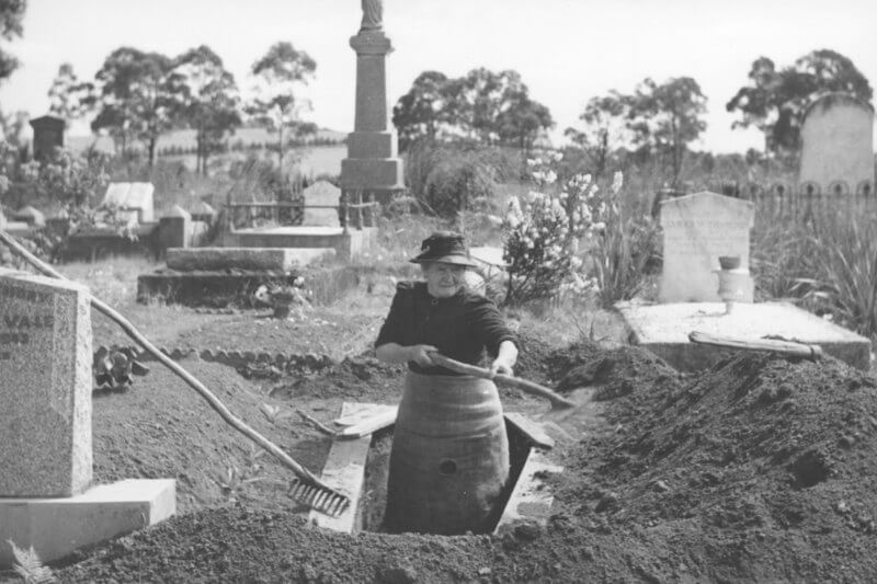 An elderley woman stood in a grave she is digging, shovel in hand