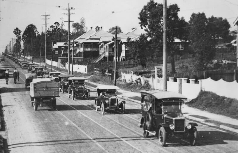 A procession of 1920s motor cars driving down a street in Brisbane