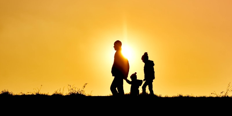 Family with young child walking across a field with sunset in the background