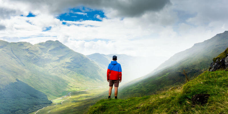 Young man looking out across a mountain range after a long climb