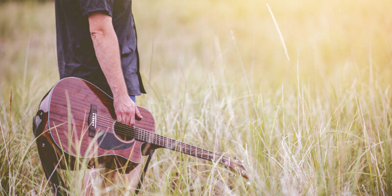 Man carrying a guitar walking through a field