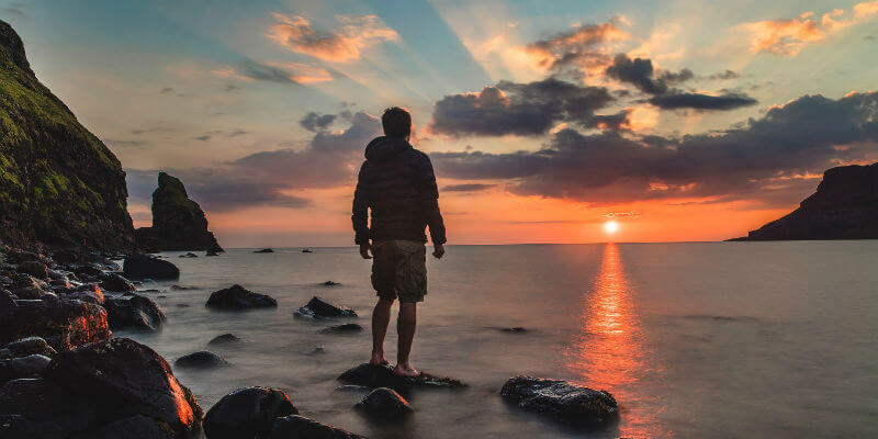 Man standing on a rock looking out to sea at sunset