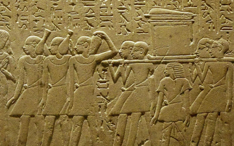 Egyptian wall carving showing mourners carrying a coffin, with heiroglyphs