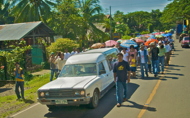 Mourners follow a hearse, carrying colourful umbrellas