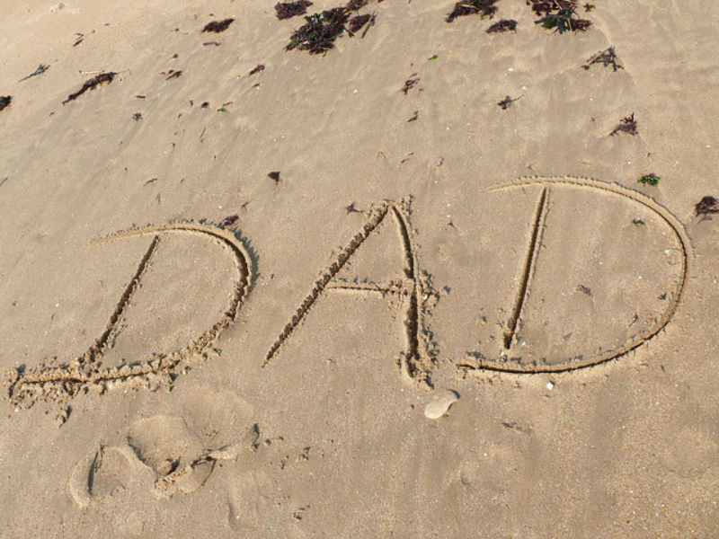 The word dad written in the sand on a  beach