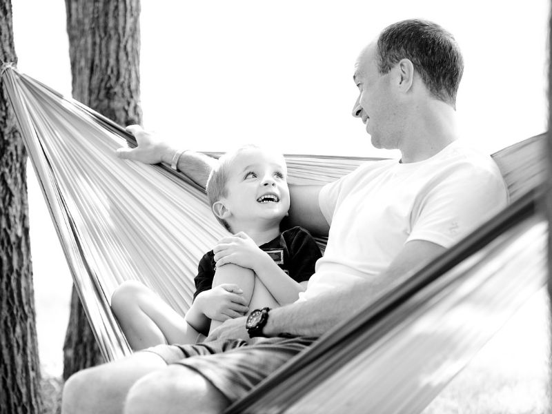 a young father and son seated on a hammock, smiling at each other