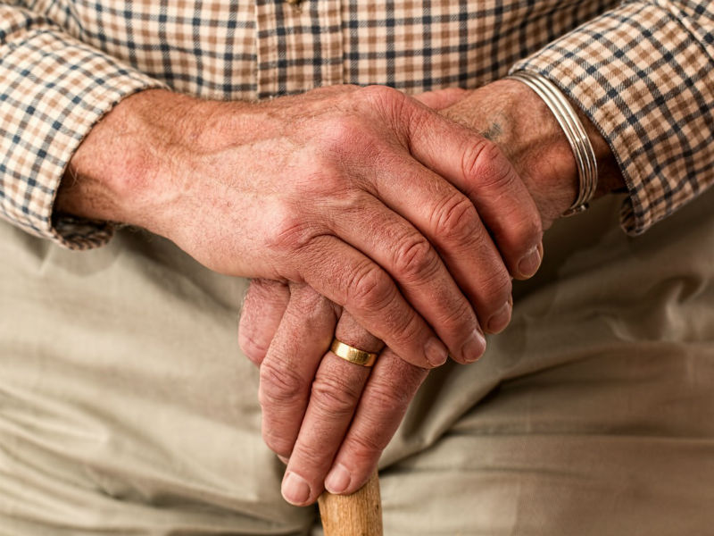 The hands of an older man, holding a walking stick