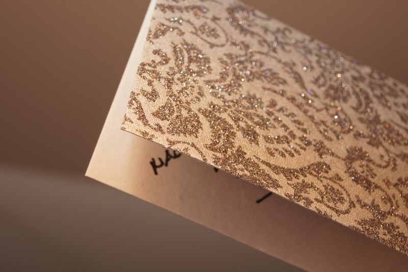 The edge of a closed Christmas card decorated with silver glitter; part of the message is visible