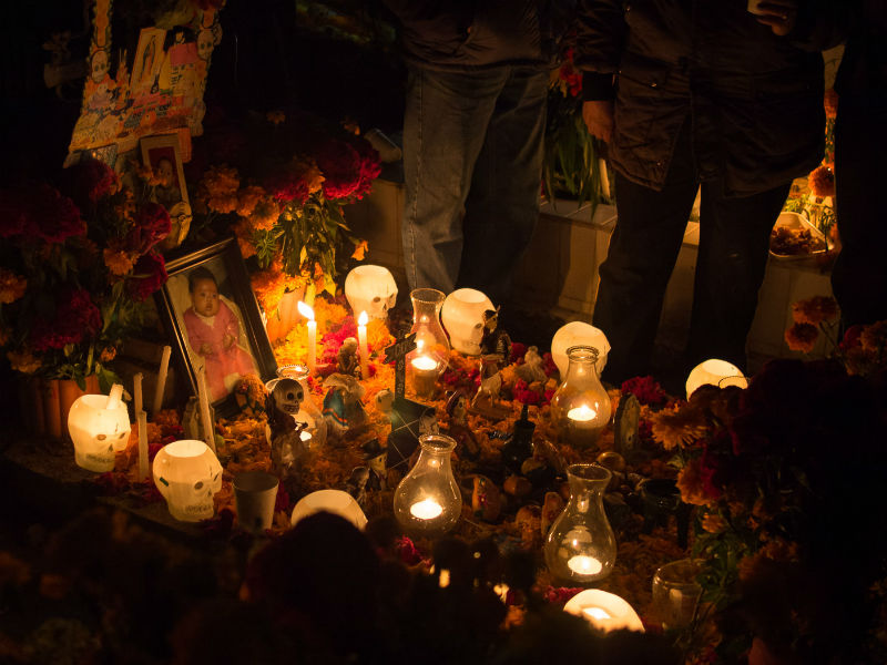 Grave decorated with candles, flowers and toy skeletons