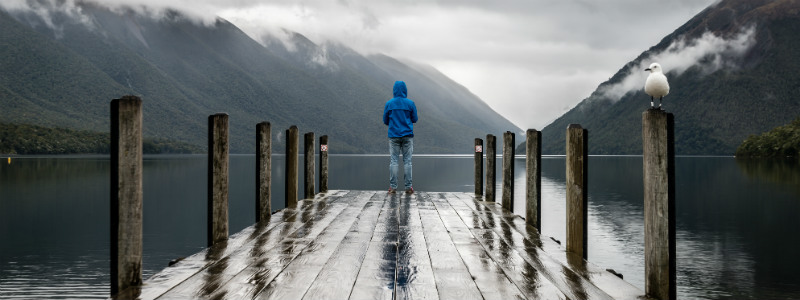 Lonely grieving man stood on the end of a pier looking out at the mountains