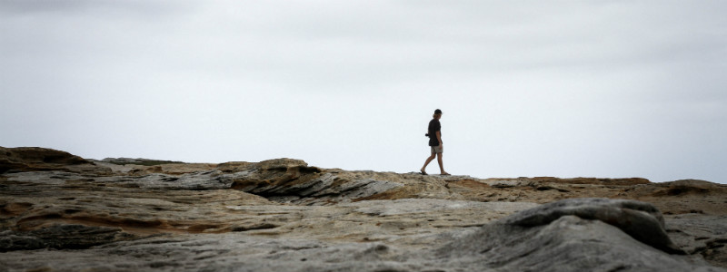 Man walking alone through a rocky landscape