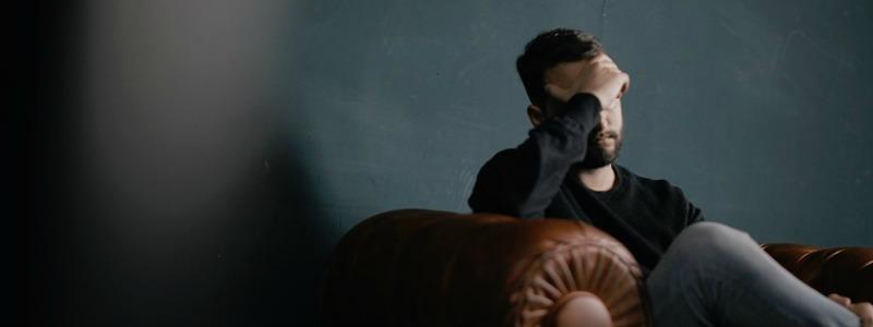 Grieving man suffering from headache