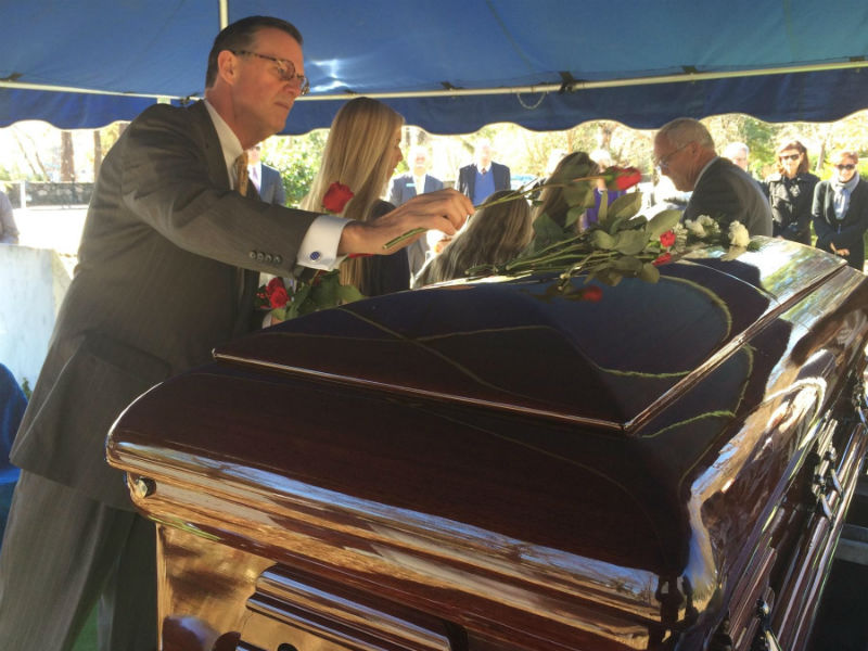 Mark T Higgins lays a flower on a casket