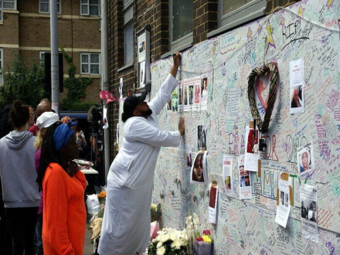 Mourners leaving messages of condolence on a memorial wall near Grenfell Tower