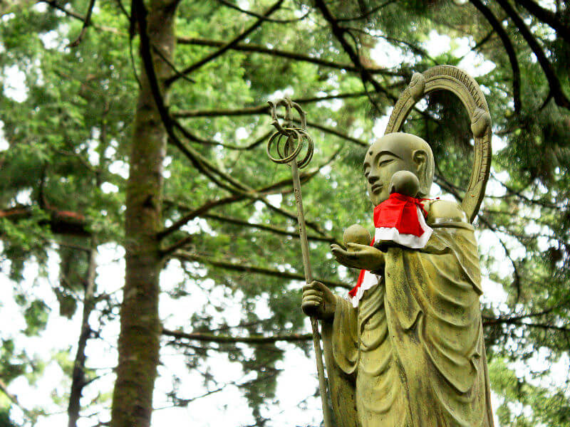A statue of Jizo holding the jewel in one hand, his shakujo staff in the other, cradling a baby in the crook of his arm