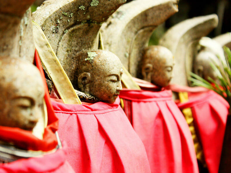 Close-up of Jizo statues dressed in red bibs