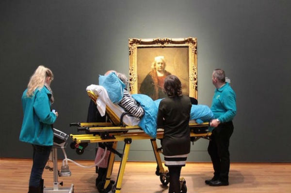 Patient on a stretcher looking at a famous painting by Rembrandt as their dying wish