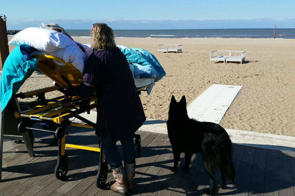 A woman stands next to her relative who is terminally ill, both looking out to sea