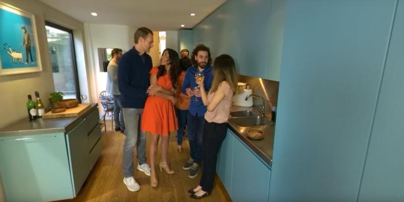 A house party; friends are gathered in the kitchen, talking and laughing