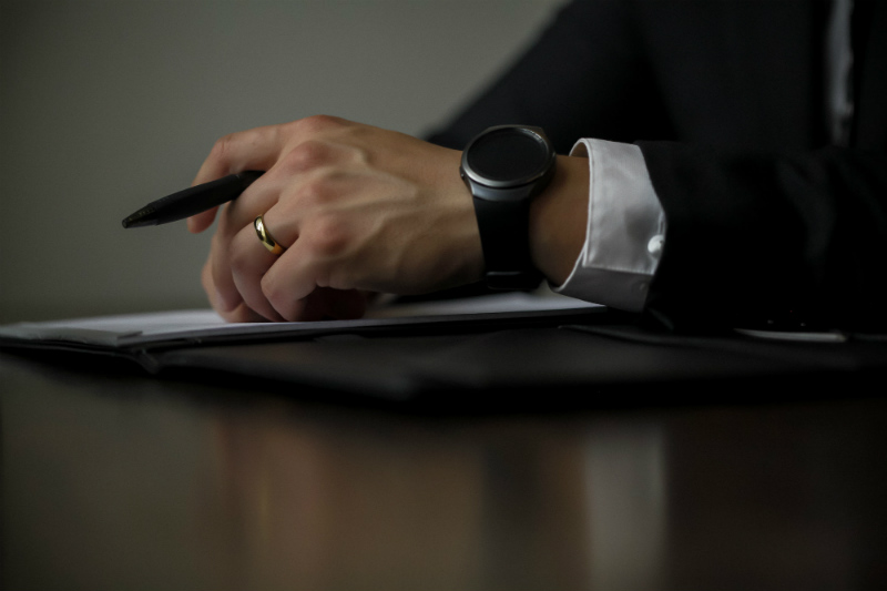 A man wearing a suit holding a pen