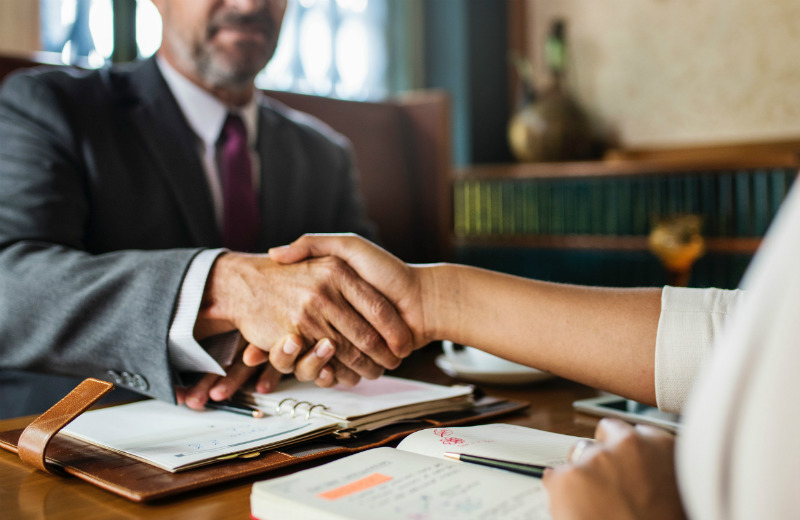 A lawyer shaking hands with their client