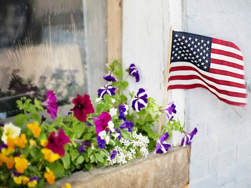 A small U.S. flag is a focal point of a patriotic window-box display