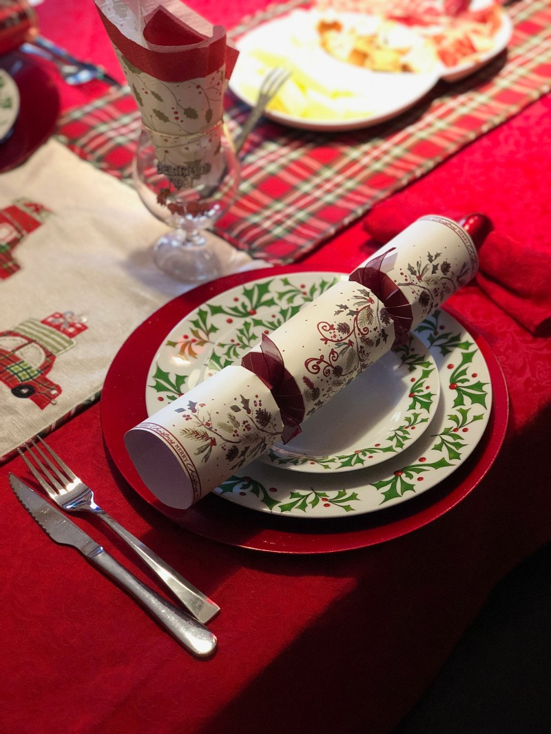 place set for Christmas dinner, with Christmas cracker and cutlery