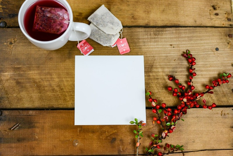 Arial view of a square of white card on a wooden table with a white mug full of red herbal tea, tea bags with red labels and a branch of red currents