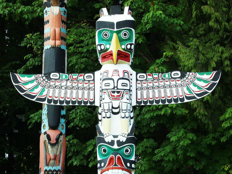 Colourful totem pole carving in the shape of a bird
