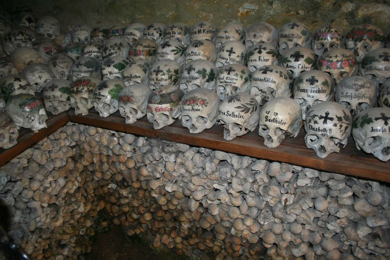 Close-op of painted skulls on a shelf in the Hallstatt Ossuary