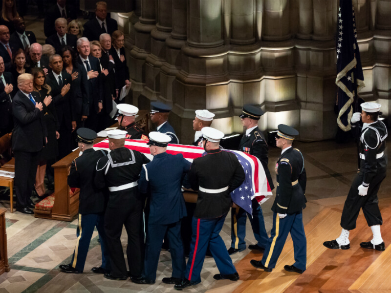 Every living president with hand on heart as President George H.W. Bush is carried out by servicemen following his funeral service