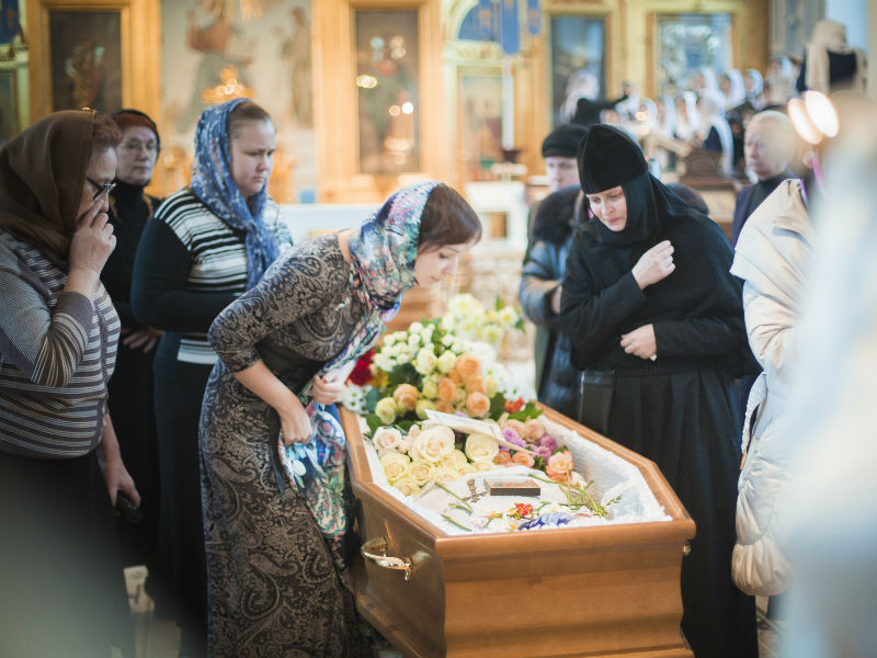 Mourners gather round an open coffin to say goodbye. One mourner leans down to kiss the body lying in the coffin