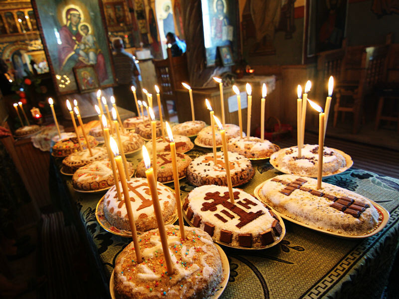 Cake-like bowls of Kolyva elaborately decorated with sweets in cross shapes, with lit candles placed in them