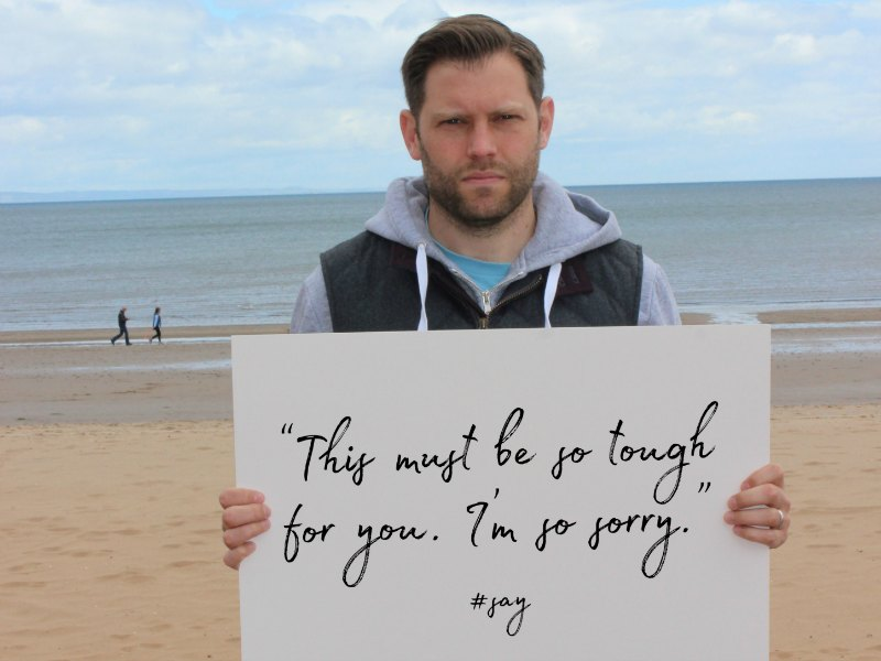 "A man at the seaside holding up a sign that reads: ""This must be so tough for you. I'm so sorry."""