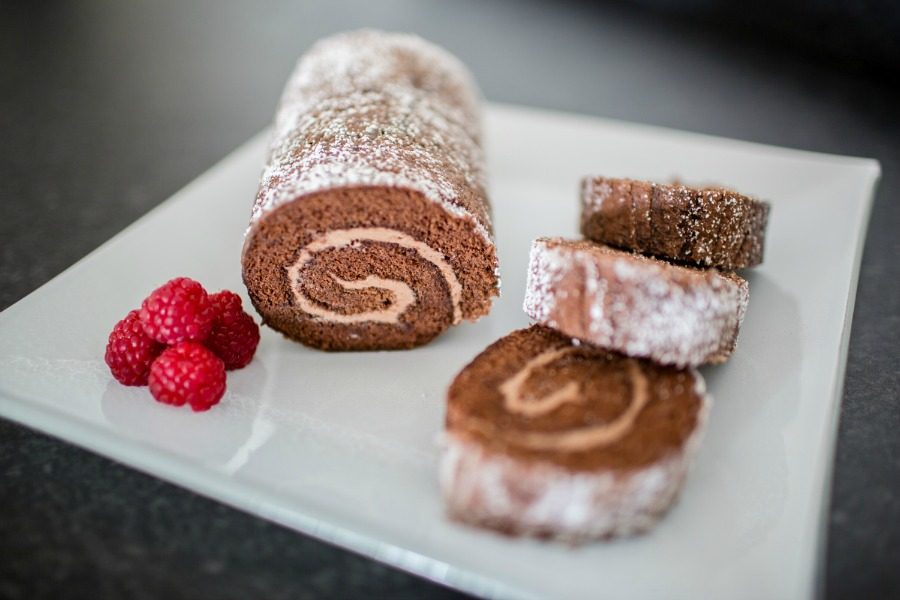 A chocolate Swiss roll dusted with icing sugar and garnished with fresh raspberries