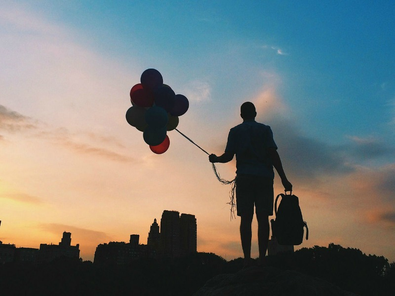 A man holding a nuch of balloons, silhouetted in the evening sky