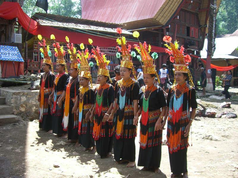Torajan dancers wearing elaborate clothing, preparing to dance