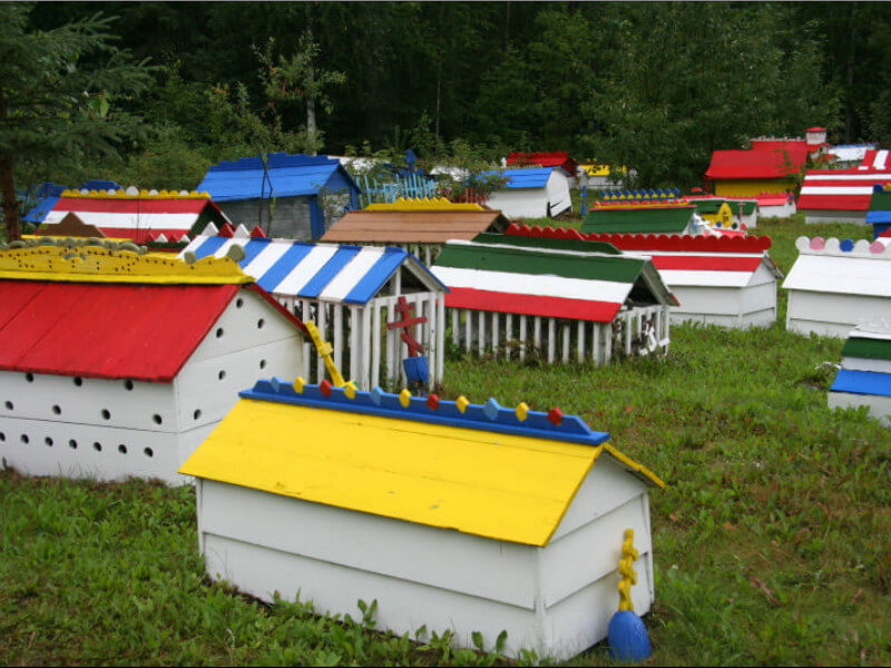 Graves covered by wooden spirit houses, painted in bright colours