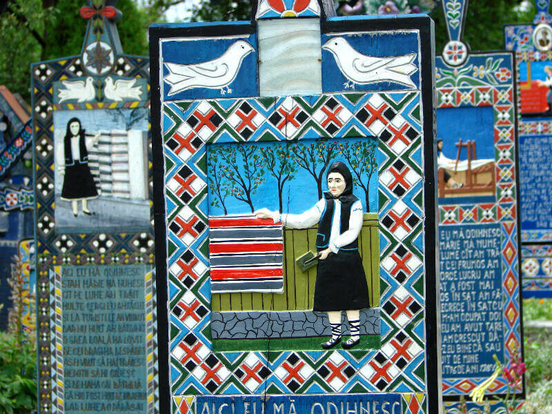 Close-up of a grave in the Merry Cemetery showing a woman in traditional Romanian dress, with dove motifs