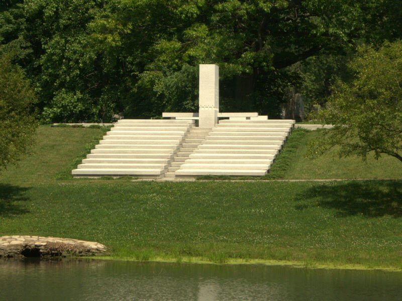 A minimalist memorial, with two sets of stairs leading down to a lake