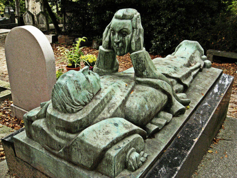 Bronze memorial statue showing a man lying down, holding a woman's head in his hands, gazing into her face