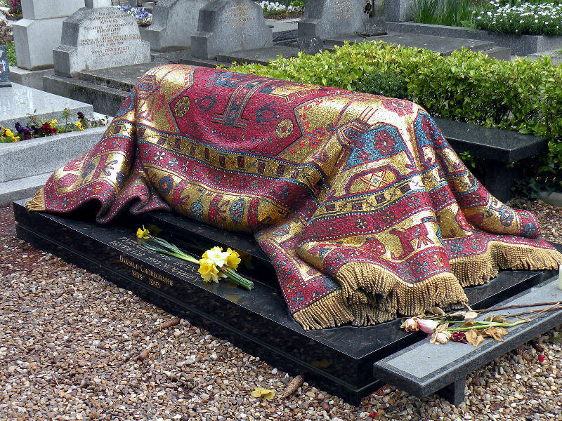 A mosaic grave which looks like a draped Persian carpet in gold, red and turquoise, the grave of Nureyev